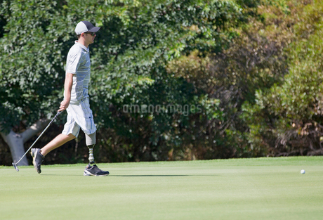 Male Golfer With Artificial Leg On Course Putting Ball On Greenの写真素材 [FYI02123431]