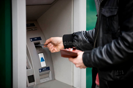 A young man using a cash machineの写真素材 [FYI02123436]