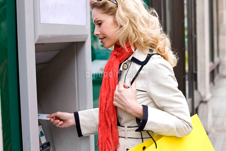 A mid adult woman using a cash machine, carrying a shopping bagの写真素材 [FYI02123437]