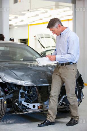 Insurance assessor inspecting damaged vehicleの写真素材 [FYI02123441]