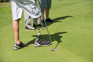 Close Up Of Male Golfer With Artificial Leg Standing By Greenの写真素材 [FYI02123486]