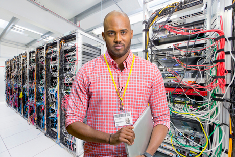 Portrait Of IT Technician In Data Centre Standing By Serversの写真素材 [FYI02123488]
