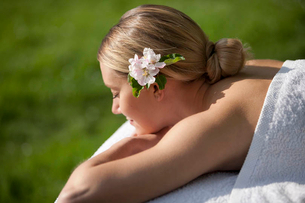 A young woman laying on a massage table with apple blossom in her hair, eyes closedの写真素材 [FYI02123491]