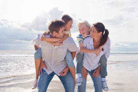Parents Giving Children Piggybacks On Beach Vacationの写真素材 [FYI02123496]