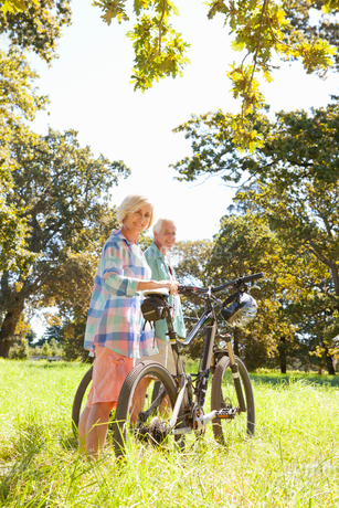 Older couple standing with mountain bikes in rural fieldの写真素材 [FYI02123507]