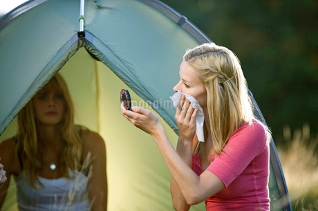 Two young women camping, one wiping her faceの写真素材 [FYI02123523]