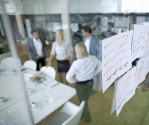 Documents Stuck To Glass Wall With Meeting In Backgroundの写真素材 [FYI02123524]