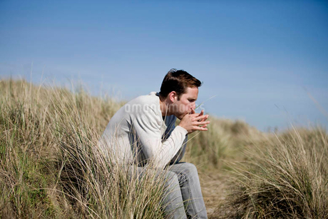 A young man sitting amongst the sand dunes, blowing on a blade of grassの写真素材 [FYI02123533]