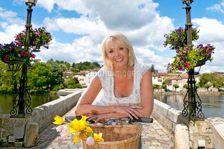 Portrait Of Mature Woman Riding Cycle Over Bridgeの写真素材 [FYI02123538]