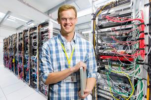 Portrait Of IT Technician In Data Centre Standing By Serversの写真素材 [FYI02123555]