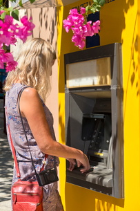 Tourist retrieving cash from ATMの写真素材 [FYI02123558]