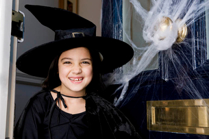 Young  girl at the front door, dressed up as a witch for Halloweenの写真素材 [FYI02123563]