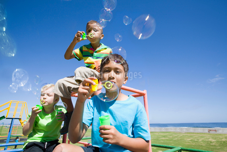 Boys blowing bubbles on monkey bars at playgroundの写真素材 [FYI02123568]
