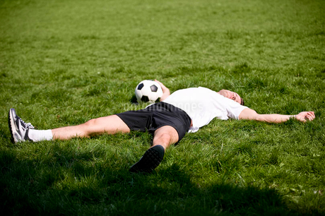 A young man lying on the grass, holding a footballの写真素材 [FYI02123569]