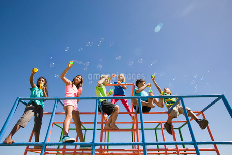Children blowing bubbles on monkey bars at playgroundの写真素材 [FYI02123570]