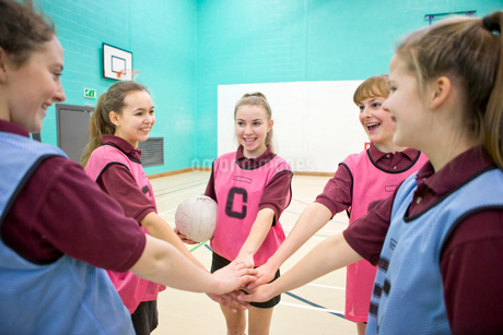 Smiling high school students touching hands in huddle before netball gameの写真素材 [FYI02123572]