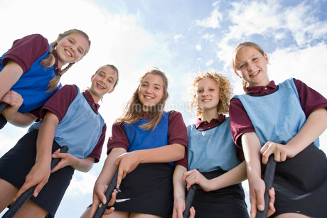 Portrait smiling middle schoolgirls playing field hockey in physical education classの写真素材 [FYI02123578]