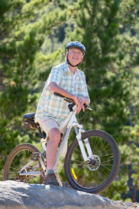 Older man riding mountain bike in forestの写真素材 [FYI02123593]