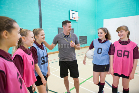 Gym teacher teaching high school students netball in gym classの写真素材 [FYI02123603]