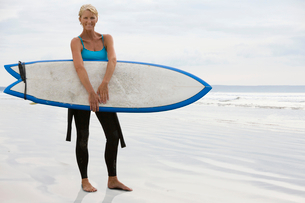 Portrait Of Mature Woman On Beach With Surfboardの写真素材 [FYI02123605]