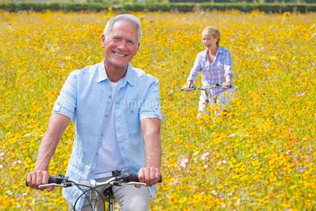 Senior Couple On Cycle Ride Through Summer Flower Fieldの写真素材 [FYI02123623]