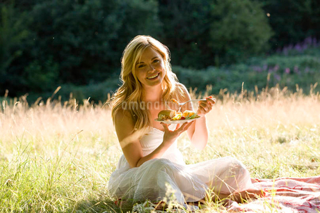 A young woman sitting on the grass, eatingの写真素材 [FYI02123643]