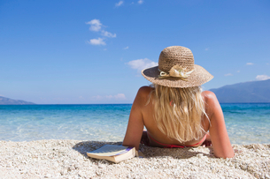 woman, looking out to sea, lying on beach with bookの写真素材 [FYI02123646]