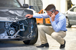 Insurance assessor or driver on mobile phone and inspecting damaged vehicleの写真素材 [FYI02123658]