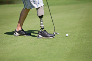 Close Up Of Male Golfer With Artificial Leg Putting Ball On Greenの写真素材 [FYI02123665]