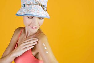 A Young Woman Rubbing Suntan Cream Into Her Armの写真素材 [FYI02123671]
