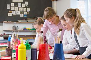 Art teacher teaching middle school students painting in art classの写真素材 [FYI02123694]