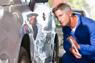 Mechanic inspecting damaged vehicleの写真素材 [FYI02123713]