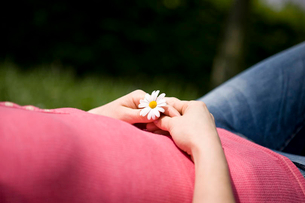 A woman lying on the grass, holding a daisy, croppedの写真素材 [FYI02123716]