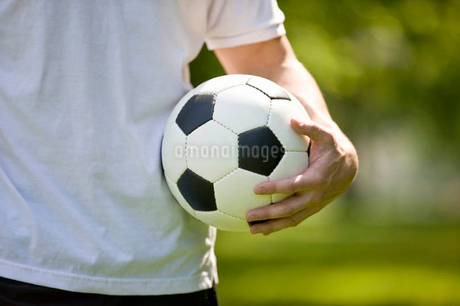 A young man holding a football, close-upの写真素材 [FYI02123724]