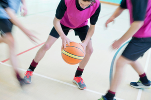 High school students playing basketball in gym glassの写真素材 [FYI02123743]