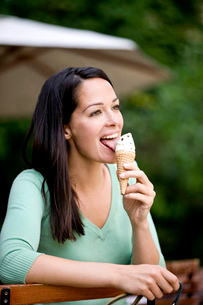 A young woman sitting outdoors, eating an ice creamの写真素材 [FYI02123746]