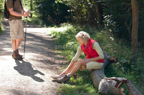 A mature couple resting beside a country path, woman massaging her sore feetの写真素材 [FYI02123750]