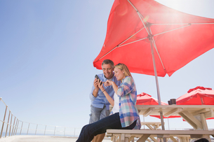 Smiling couple using cell phone under umbrella at waterfront tableの写真素材 [FYI02123753]