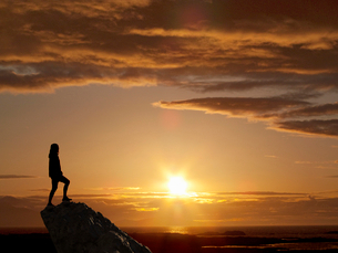 Silhouette Of Woman Standing On Mountain Peak At Sunsetの写真素材 [FYI02123760]