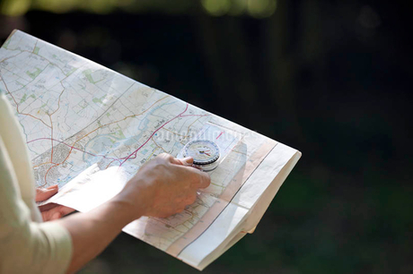 A woman holding a map and compass, close upの写真素材 [FYI02123763]