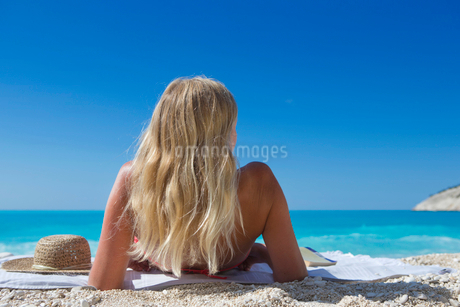 woman, looking out to sea, lying on towel on sunny beachの写真素材 [FYI02123766]