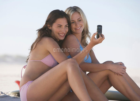 Two young women in bikinis taking a picture with their mobile phoneの写真素材 [FYI02123774]