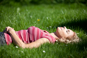 A mature woman laying in the grass in summertimeの写真素材 [FYI02123816]