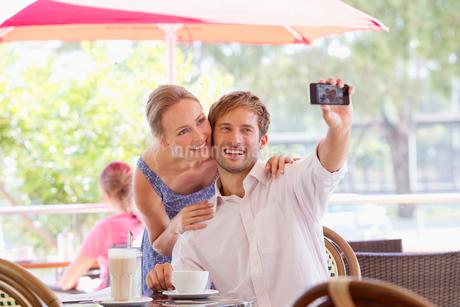 Couple taking selfie in outdoor cafeの写真素材 [FYI02123821]