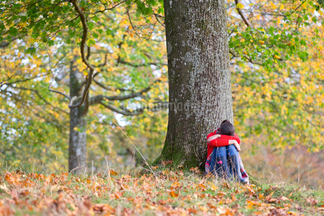 Young girl, looking sad, leaning against tree, in autumnal parkの写真素材 [FYI02123824]