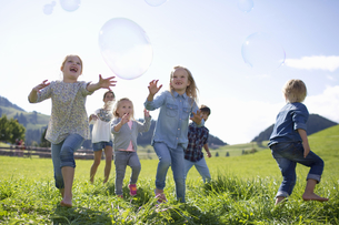 Children Chasing Giant Bubbles In Countrysideの写真素材 [FYI02123839]