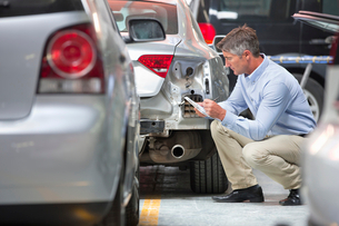 Insurance assessor inspecting damaged vehicleの写真素材 [FYI02123847]
