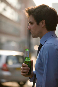 A businessman holding a bottle of beerの写真素材 [FYI02123853]