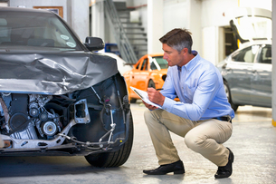 Insurance assessor inspecting damaged vehicleの写真素材 [FYI02123864]