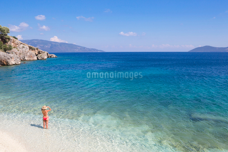 Woman , looking out to sea, standing in sea on sunny beachの写真素材 [FYI02123886]